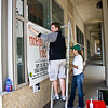 Tiffany Dubec and Justin Roth of Syndicate Graphics install the signs (developed or created?) by TPM inc.