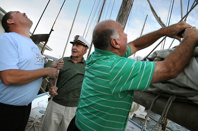 Dipping his bucket into the harbor, Captain Dainels goes around his skipjack for stern to bow rinsing off the deck. Photo By Maximilian Franz 9-07-09