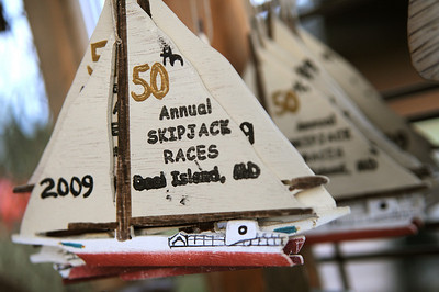 Before dawn, small hand crafted skipjack ornaments made by artist Mark A. Pleasanton blow in the cool breeze just inside the gates to the raceboats. Photo By Maximilian Franz 9-07-09