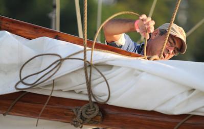 "A crewmember of the ""Martha Lewis"" checks the lashings on the main sails. Photo By Maximilian Franz 9-07-09"