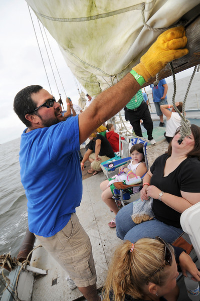 Once out of the harbor, crew members Terry Danniels Jr( Blue Shirt) and Reverand Bob Daniels(Green Shirt) unlash the main sail to head to the starting line. Photo By Maximilian Franz 9-07-09