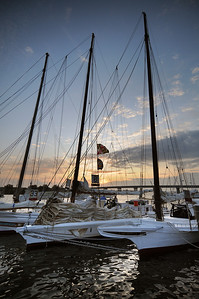 The sun rises behind the masts of the Skipjacks in Chance harbor as crew members ready their ships for the 5oth Annual Skipjack Race. Photo By Maximilian Franz 9-07-09