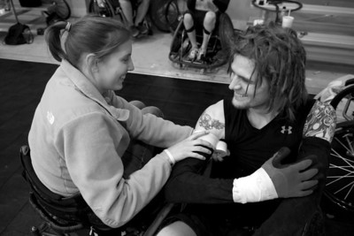 Austin's girlfriend, Lindsey, helps him wrap tape around his arms during a wheelchair rugby practice.
