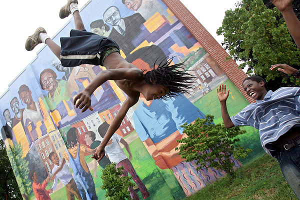 Raekwon McMann, 10, of Baltimore, does a backflip in a neighborhood square with some help from his friend Alonta Johnson, 14, on Friday, June 29, 2007. Chris Ammann/Examiner