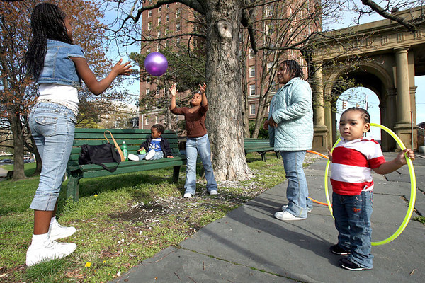 Chris Ammann/Baltimore Examiner Ashani Skinner, 12, left, throws a ball around with India Harris, 9, center, and Erin Sanders, 8, in Druid Hill on Tuesday, April 11, 2006. Jerrel Gardner, 1, seated on the bench, and Nysira Matthews, 1, also enjoy the nice weather with their day care group.