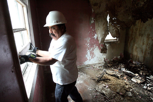 Jose Cortes, of Columbia, works to pry loose a window inside a home that is to be demolished to make way for his new home through Habitat for Humanity in Jessup on Friday, June 15, 2007. Chris Ammann/Examiner