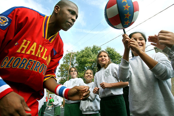 """Chris Ammann/Baltimore Examiner Dwayne """"Swoop"""" Simpson, left, of the Harlem Globetrotters watches as Alyssa Lazaro, 10, passes the spinning ball on a pen to the next child in line at St. Michael the Archangel School in Baltimore on Thursday, Oct. 5, 2006."""