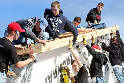 Chris Ammann/Baltimore Examiner University of Maryland marching band member Bobby Becker, left, of Frederick, nails in the barge rafter, using the support of his band-mates who hold the board in place while working for Habitat for Humanity at the Musicians' Village in New Orleans, La., on Monday, Jan. 8, 2007.
