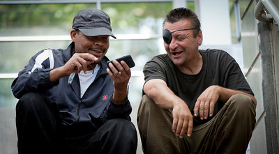 Mr. Bias (left), a homeless person on the streets of Arlington, Va., shows Johnny, another homeless person, photographs he took on his smart phone, 19 June 2013.  (Photo by Bernardo Fuller)