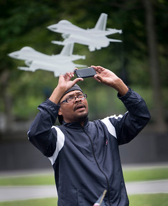 Mr. Bias, a homeless person on the streets of Arlington, Va., takes photos of military jets frosted into a glass display with his smart phone at the Air Force Memorial in order to tweet later, 19 June 2013.  (Photo by Bernardo Fuller)