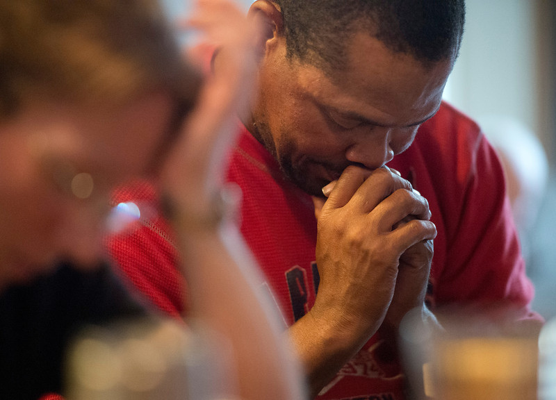 Mr. Bias, a homeless person on the streets of Arlington, Va., prays as he partakes in a bible study at the home of Christian family who invites him to their home every week, 19 June 2013.  (Photo by Bernardo Fuller)