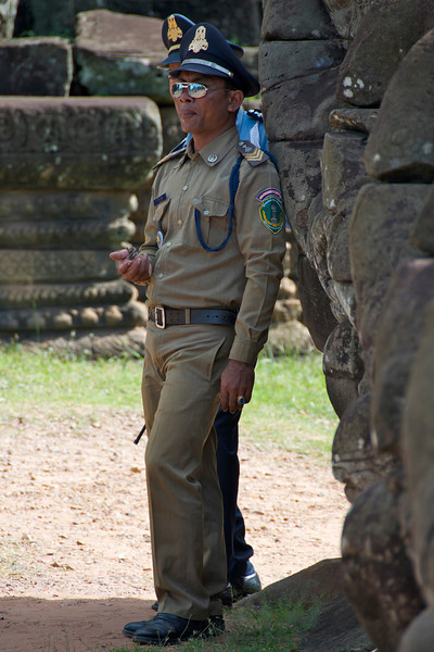 Apparently police sunglasses transcend cultural barriers. (Or maybe he was a park ranger; whatever the case it's a pretty impressive uniform.)<br /> <br /> Angkor Wat, Cambodia