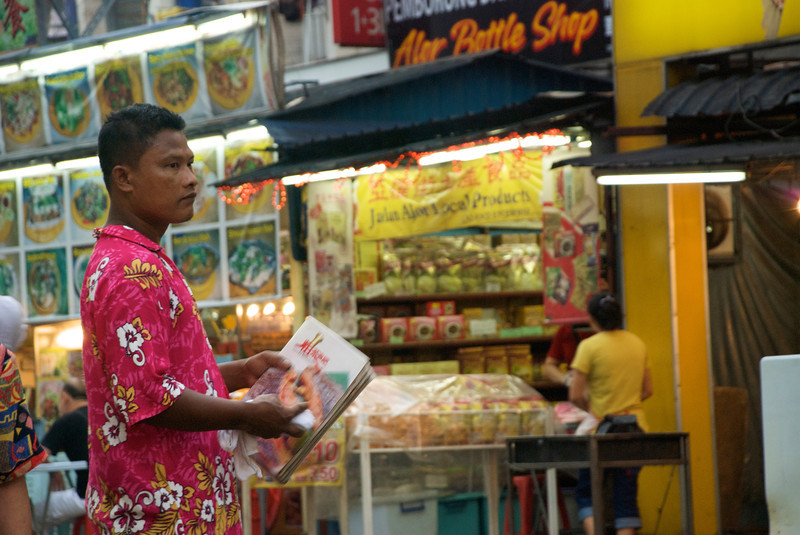 A waiter/shill has menus ready to entice someone to his restaurant. The entire block was lined with food carts and restaurants, most with outdoor seating.<br /> <br /> Kuala Lumpur, Malaysia