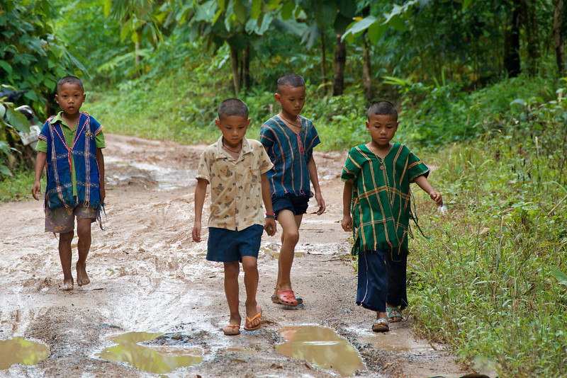 Karen villagers walking down what was actually a good section of the only road. The boys in stripes are wearing traditional shirts.<br /> <br /> Laiwo, Thailand