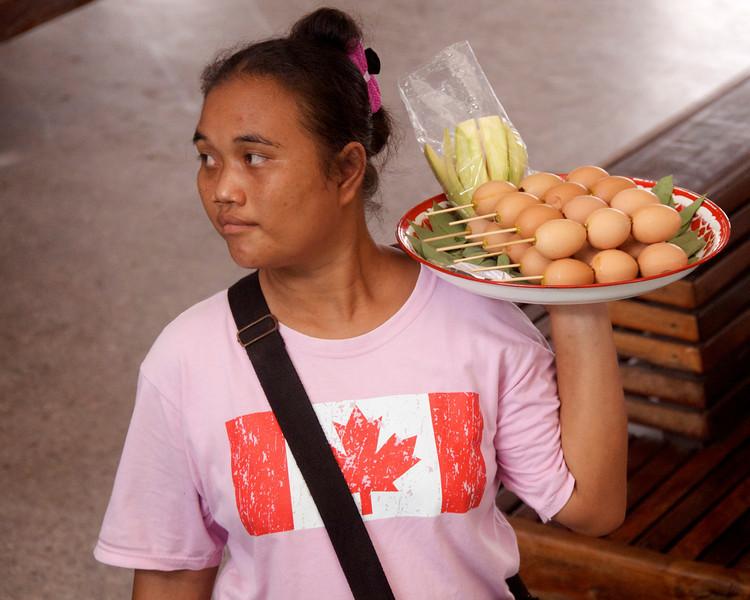 One of the many salespeople at the bus station. They go from bus to bus selling a variety of food and drink either through the windows or by briefly boarding the bus and walking the aisle.<br /> <br /> Khon Kaen, Thailand