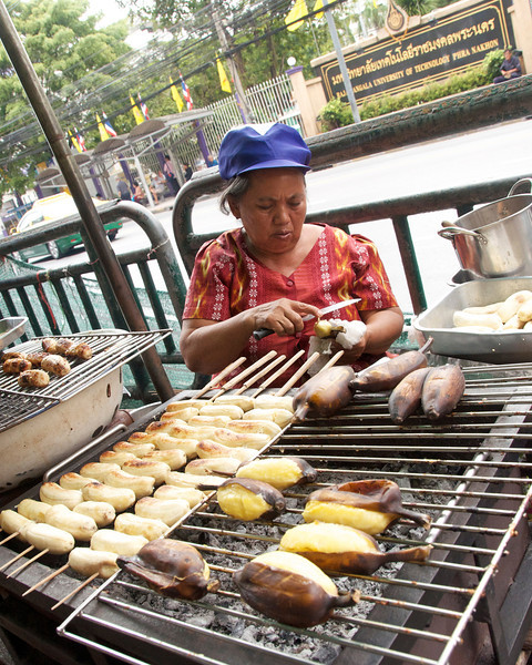 Roasted banana vendor. I love these and probably cleared out her stock after taking the photo.<br /> <br /> Bangkok, Thailand