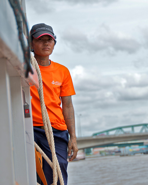 One of the workers on a Chao Phraya commuter job. His job is to stay in the back of the rather lengthy boat and signal the driver with shrill whistles as the driver maneuvers close to piers. He then jumps onto the pier and secures the boat for the brief time it drops off and picks up passengers. Then he unties the boat and it's on to the next stop. <br /> Bangkok, Thailand