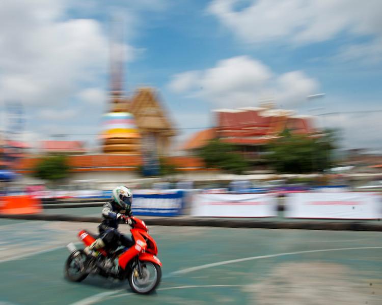 More moto racing against the backdrop of a Wat (temple).<br /> <br /> Khon Kaen, Thailand