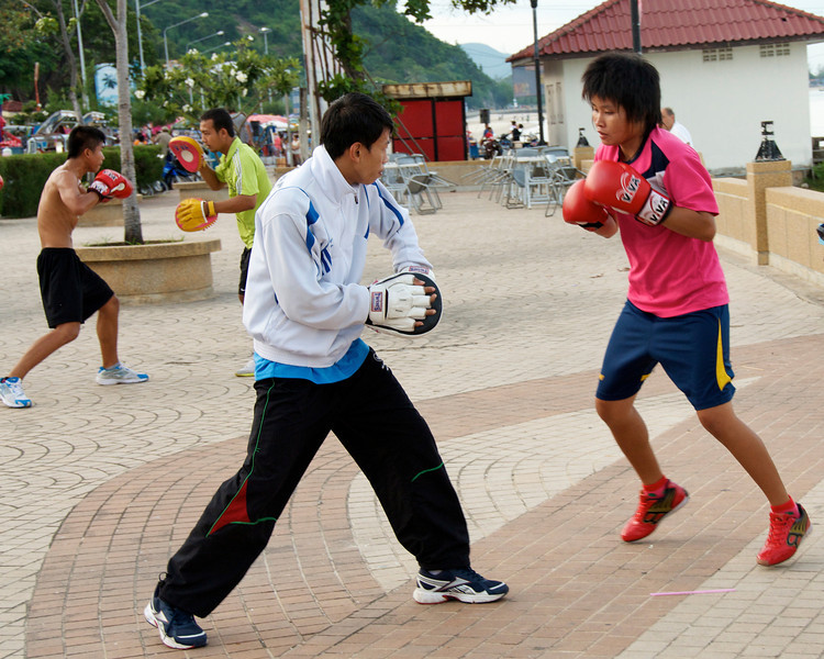 "Boxers training on the boardwalk. I was surprised that it was western style and that women were training, as Thai women are relatively rare in Muay Thai (Thai kickboxing). I think they may have been from a local sports school. The coach in the white warm-up jacket was nice enough to hold pads for me for a round. I sent him scurrying for cover yelling ""hands only!"" when I faked a front kick. His friends are probably still teasing him about that.<br /> <br /> Prachuap Khiri Khan, Thailand"