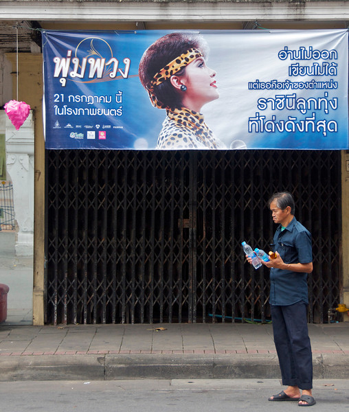 "Man paused in front of an ad for a movie about Pumpuang Duangchan, the late ""queen of luk thung,"" a form of Thai country music.<br /> <br /> Bangkok, Thailand"