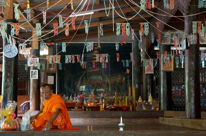 Monk with offerings at the village Wat (temple).<br /> <br /> Laiwo, Thailand