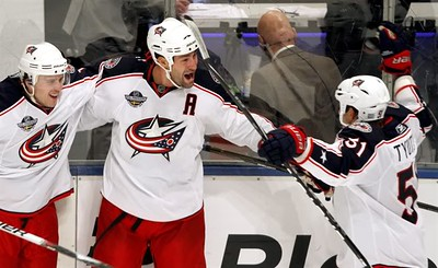 Columbus Blue Jackets' Ethan Moreau (middle) celebrate scoring the overtime game winning goal, with teammates Kris Russel (left) and Fedor Tyutin (right), during the sudden death of a NHL hockey game against Columbus Blue Jackets, in Stockholm, Sweden, Saturday, Oct. 9, 2010. (AP Photo/Niklas Larsson)