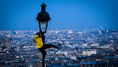 Soccer playing bouncing a ball on Montmartre, above Paris, France