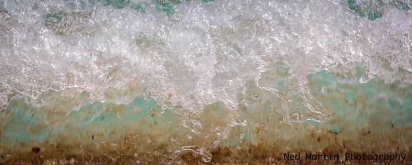 Wave pulling up sand and pebbles at Palm Beach, FL