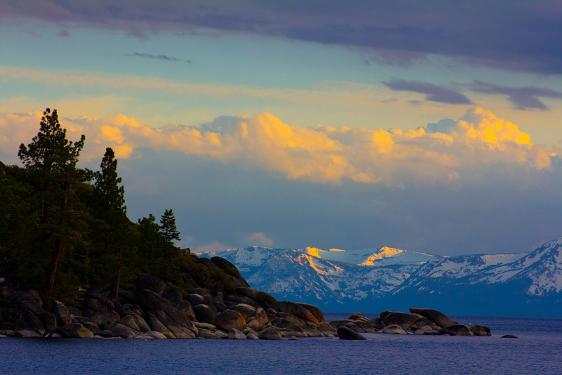 Lake Tahoe June 17, 2011<br /> <br /> This was captured on the northeast side of Lake Tahoe. I had been driving around the Lake for several hours when the sun started to set. I saw the mountain range in the background but what makes shots like this for me is finding a focal point in foreground. I walked the beach for about a half hour and then found this rock formation and trees. It gives it the depth of field that I was looking for. You have the rocks in the foreground, the mountain range behind that and finally the clouds with the yellow glow of sunset.  I sat here for about an hour and a half just taking in the view.