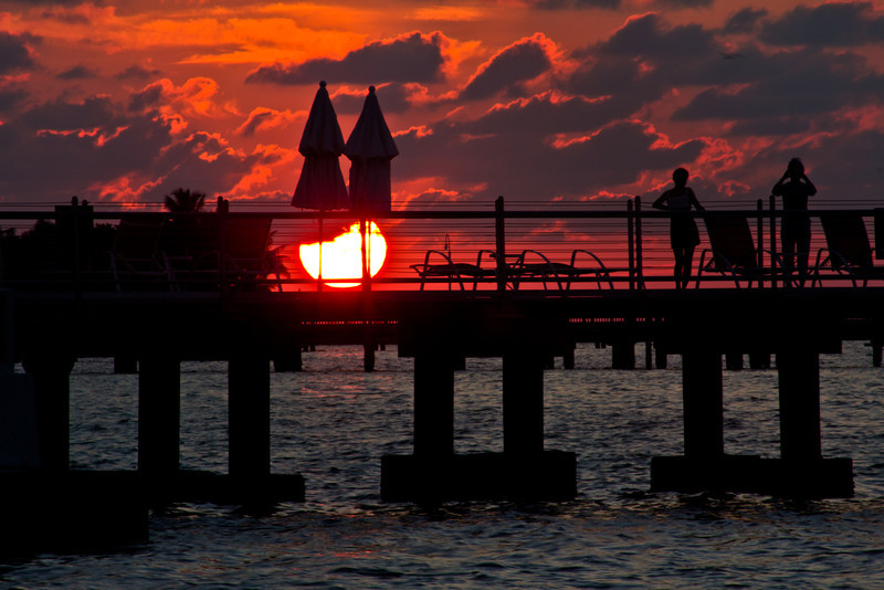 "Sunrise Key West 9.16.11<br /> <br /> This was the first morning of this trip. I had been to this location last year for a couple sunrise but I wasn't exactly sure where the sun was going to rise this morning. The last time I was there it came up more to the right of this pier, so I just waited and luckily it came up right in line with the pier in front of me. I saw the people standing there and then the two umbrellas that reminded me of the Twin Spires at Churchill Downs. I positioned myself to have the sunrise right in the middle of the ""Spires"" and this is what I captured."
