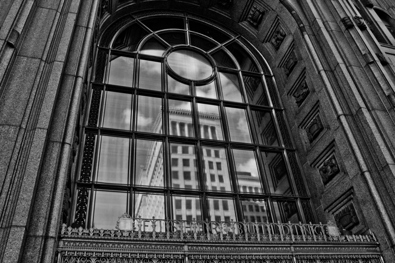 Detroit 6.7.12<br /> <br /> This is a reflection in the front window above the entrance of the Fisher Building. I had been working in the building and decided to walk around it and see what I could capture and luckily I looked up and saw this reflection. I of course turned it Black and White, but the image was not adjusted other than color, I didn't add the reflection.