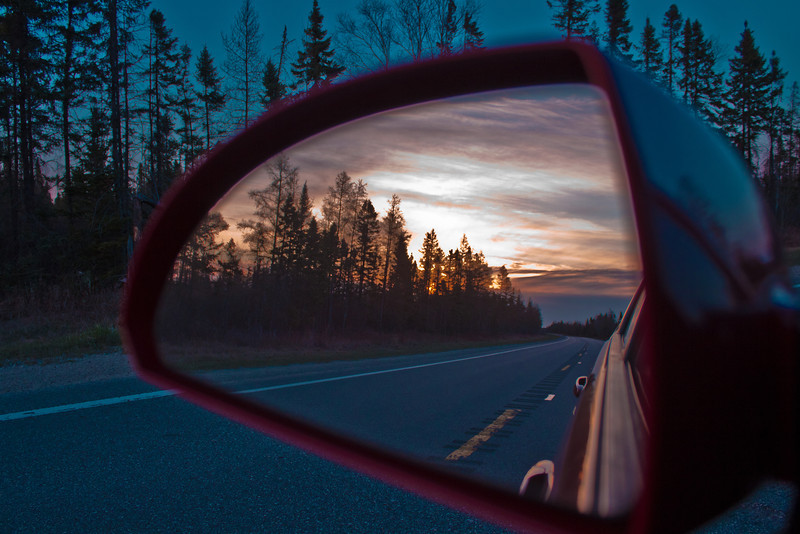 I captured this just outside of Newberry in the U.P. of Michigan. I have shot may of these mirror shots, but this is my favorite to date. I had just worked a full day in Marquette and was just about to arrive at my hotel. I looked in the mirror and saw this wonderful sunset and clouds. There was no one else on the road, so I just stopped in the middle of highway 28, got my camera ready and captured this image. I was trying to capture the difference between the treeline looking at sunset (in the mirror) and looking away (above the mirror).