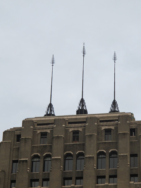 Sunday, July 17, 2011. Waiting with mom downtown to catch a bus home, I notices these beautifully detailed spires (flag poles?)on top one of the buildings.