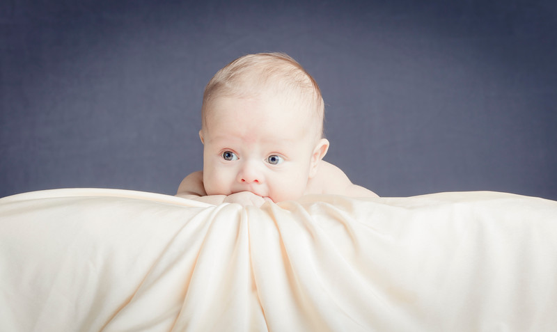 Newborn baby climbing bright fabric with sparkle eyes