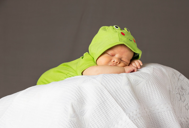 New Born Baby Sleeping wth green dress on white blanket