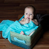 Newborn baby inside Fabric basket  with blue fabric