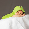New Born Baby Sleeping wth green dress on white blanket