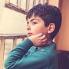 Boy looking through window inside house in Iraq