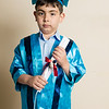 Small boy graduation from kindergarten with blue formal dress with rolled paper in his hand