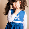 Small Caucasian girl putting her hand on her cheek Posing with blue dress standing inside studio