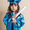 Portrait of small caucasian girl graduation from kindergarten with white rolled paper in hand