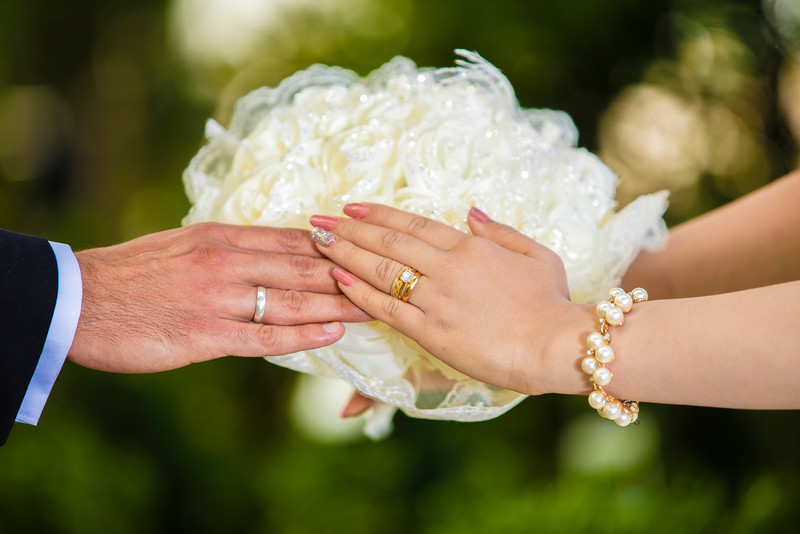 Bride And Groom hands holding wedding flower with thrm marriage rings in hand