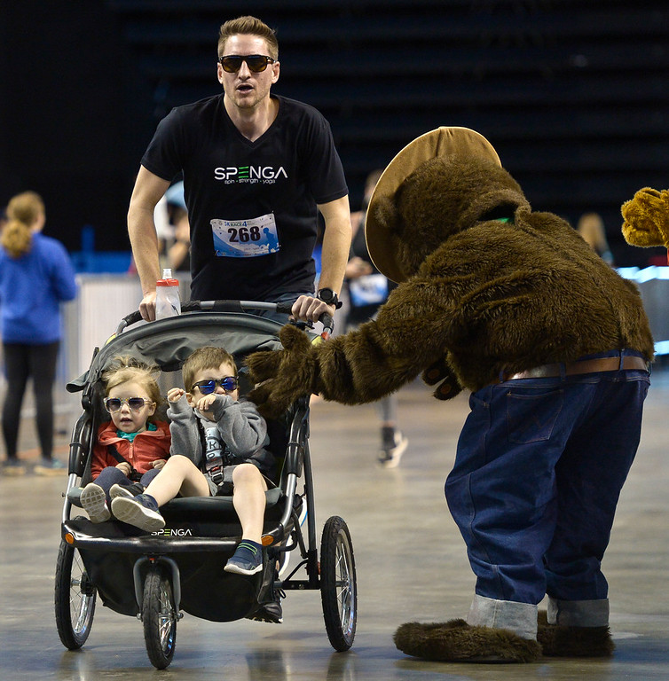 . BROOMFIELD, CO - APRIL 7: Brandon Camp pushes his kids Aubrey, 2, and Evan, 4, with him across the finish line at the Frank Shorter RACE4Kids\' Health 5K & Expo at the 1st Bank Center April 7, 2019. RACE4Kids was celebrating its 10th anniversary. To view more photos visit dailycamera.com. (Photo by Lewis Geyer/Staff Photographer)