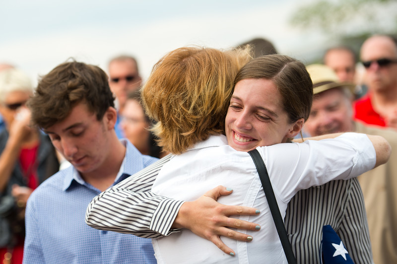 """Siena Faughnan receives a hug during North Metro Fire's annual 9/11 memorial ceremony at the Broomfield Amphitheater on Sunday. Siena Faughnan's father, Chris Faughnan, was among those killed in the terrorist attacks fifteen years ago.<br /> More photos:  <a href=""""http://www.dailycamera.com"""">http://www.dailycamera.com</a><br /> (Autumn Parry/Staff Photographer)<br /> September 11, 2016"""
