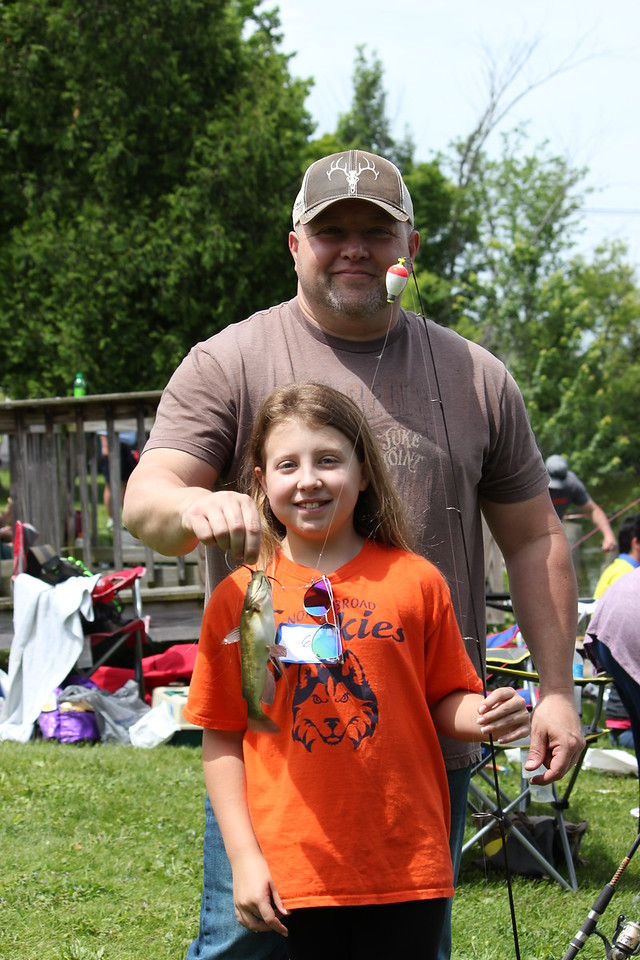 Charles Pritchard - Oneida Daily Dispatch Kenidi Bloss, 9, and her father Scott show off their catch at the 68th annual Sherrill Kids Fishing Derby on Saturday, June 9, 2018.