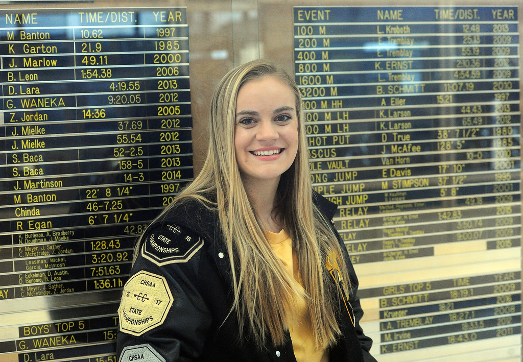 . Junior Kenadi Krueger, the 2018 RH Girls All-Area Cross Country Runner of the Year, stands in front of Thompson Valley\'s school record board. (Colin Barnard/Loveland Reporter-Herald)