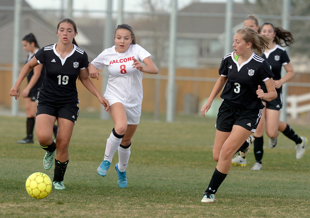 . Skyline\'s Brie Musser chases after the ball between Berthoud\'s Alex Luth, left, and Chloe McIntosh in the first half Monday at Skyline High School. To view more photos visit bocopreps.com.  Lewis Geyer/Staff Photographer April 17, 2017