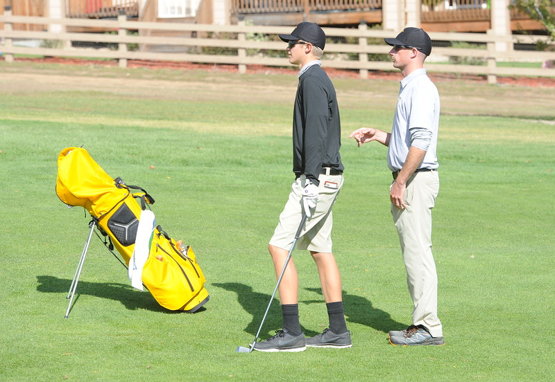 Thompson Valley's Darren Edwards prepares for his second shot on the 15th hole with coach Derek Shagin during the second and final round of the 4A Boys State Golf Championship on Tuesday at Raccoon Creek in Littleton.
