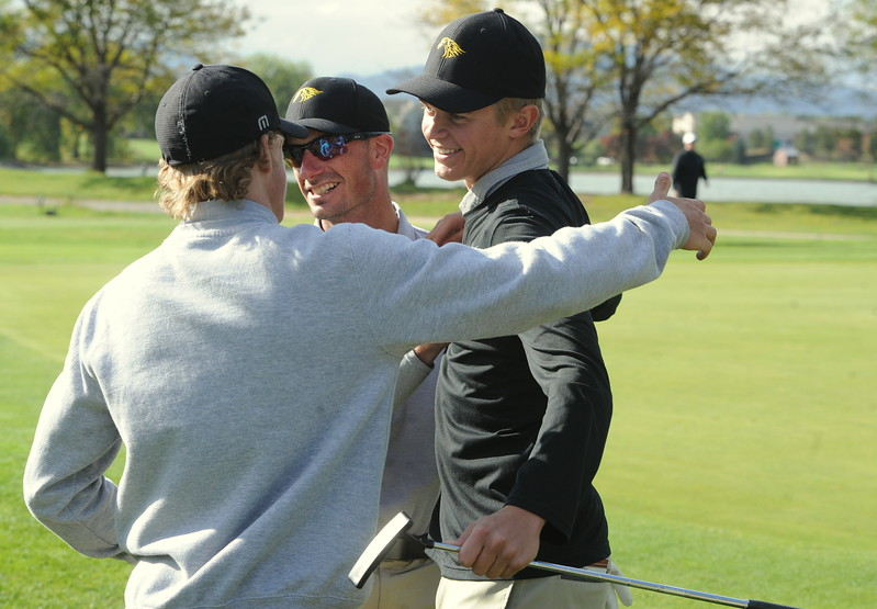 Thompson Valley's Darren Edwards (right) is embraced by his coach, Derek Shagin (middle), and teammate Nate Dwyer after winning the 4A Boys State Golf Championship on Tuesday at Raccoon Creek in Littleton.
