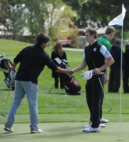 Berthoud's Cameron Poll, right, shakes hands with a fellow competitor Mountain View's Wes Weber surveys the seventh green during the second and final round of the 4A Boys State Golf Championship on Tuesday at Raccoon Creek in Littleton.